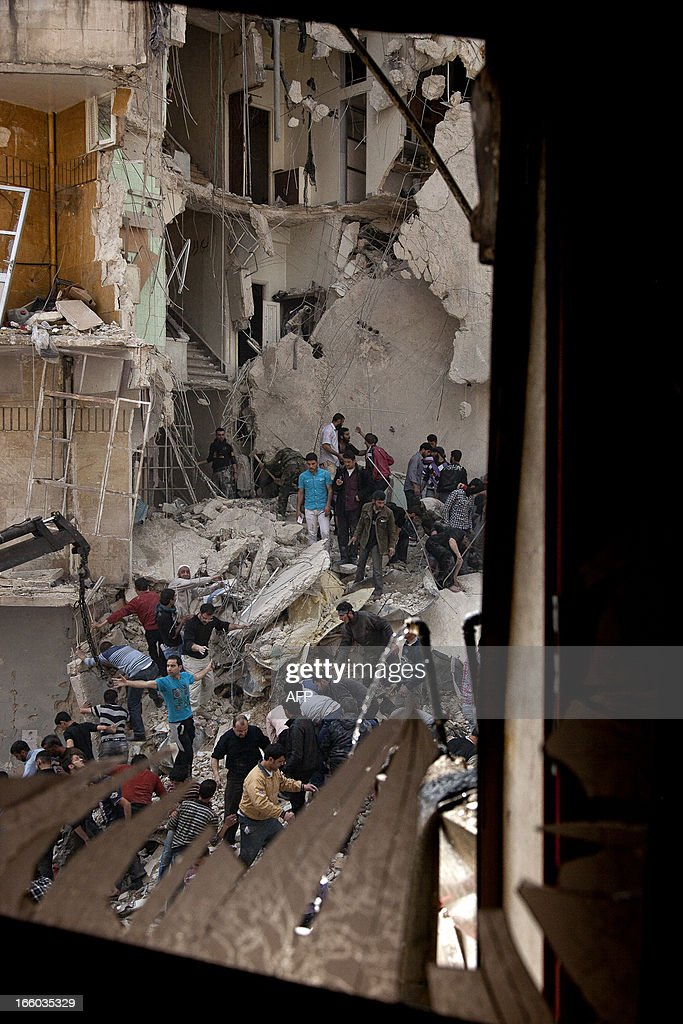 Syrians try to remove large pieces of concrete with the help of a crane to free those trapped under the rubble following an air strike by government forces on April 7, 2013 that destroyed two five-storey apartment blocks and severely damaged ten buildings in a residential neighbourhood of the northern Syrian city of Aleppo, according to eyewitnesses. Warplanes also raided Yabrud near Damascus and Qusayr in the central province of Homs, as tanks shelled rebel enclaves in Homs city the same day.