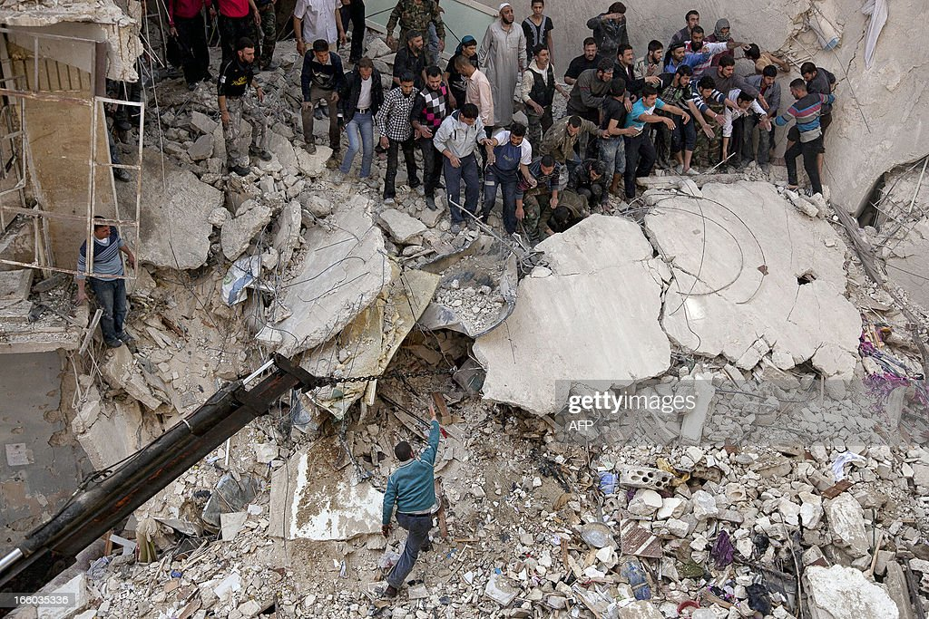 Syrians try to remove large pieces of concrete with the help of a crane to free those trapped under the rubble following an air strike by government forces on April 7, 2013 that destroyed two five-storey apartment blocks and severely damaged ten buildings in a residential neighbourhood of the northern Syrian city of Aleppo, according to eyewitnesses. Warplanes also raided Yabrud near Damascus and Qusayr in the central province of Homs, as tanks shelled rebel enclaves in Homs city the same day. AFP PHOTO / VICTOR BREINER