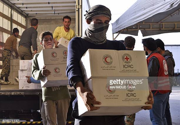 Syrians unload boxes from a lorry after an aid convoy of the International Committee of the Red Cross and the Syrian Arab Red Crescent entered the...