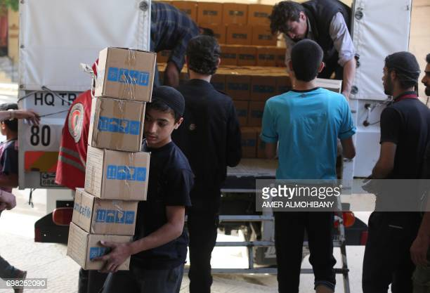 Syrians unload boxes of aid donated by UNHCR in the rebel held and besieged town of Harasta in the Eastern Ghouta region outside Damascus on Jun 19...