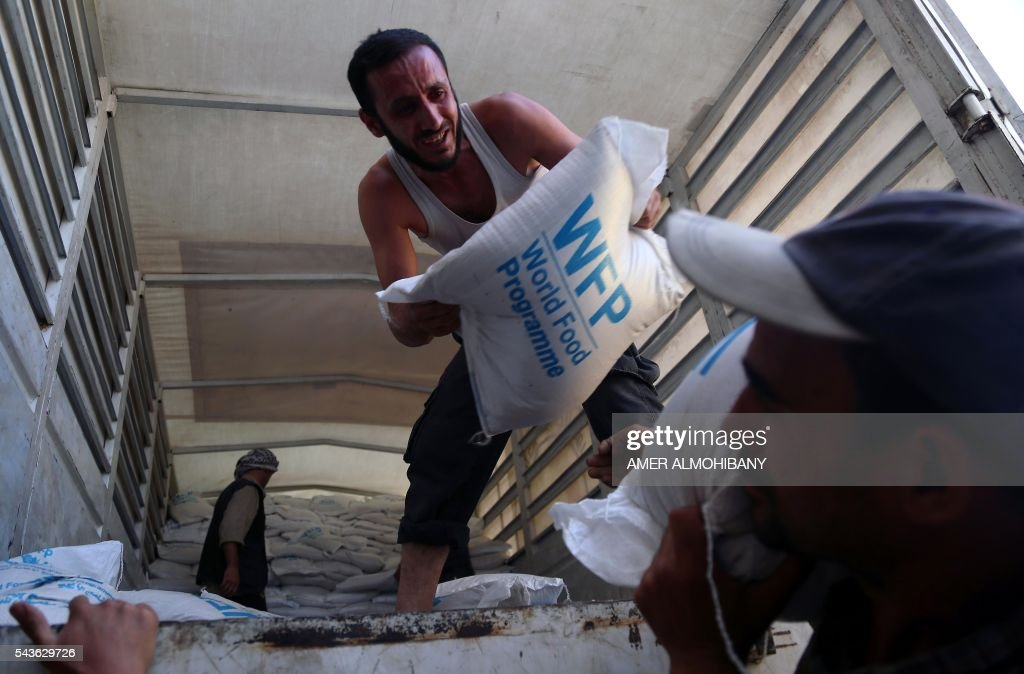 Syrians unload sacs of food from a Syrian Arab Red Crescent truck in Zamalka, a besieged rebel-held town east of the capital Damascus, on June 29, 2016. A convoy entered the besieged Syrian towns of Zamalka and Erbin near Damascus, the first aid delivered to them since 2012, the International Committee of the Red Cross told AFP. ICRC added it was delivering 37 trucks of aid in partnership with the United Nations and Syrian Arab Red Crescent. The convoy includes food parcels, wheat flower, and hygiene kits for the 20,000 people living in the besiged towns. ALMOHIBANY
