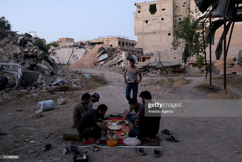 Syrians wait Iftar time to break their fasts between collapsed buildings during the Islamic holy month of Ramadan at Cobar district of eastern Goutha...