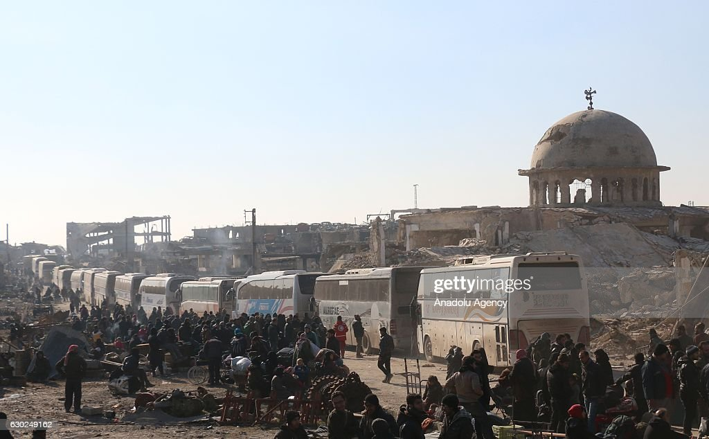 Syrians wait to be evacuated from the east part of Aleppo that had been under siege by Assad Regime forces and its supporter foreign terrorist groups at a crossing point in Amiriyah district of Aleppo, Syria on December 19, 2016 as a convoy, including buses and ambulances wait for them.