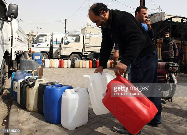 Syrians wait to fill their jerry cans with diesel at a petrol station in Damascus on March 13 2012 AFP PHOTO/LOUAI BESHARA