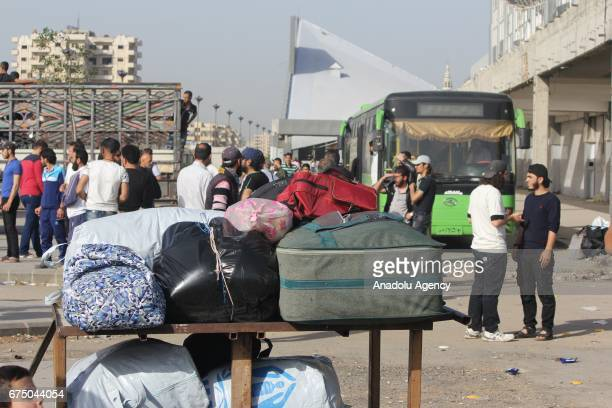 Syrians wait with their belongings as some vehicles in the 7th evacuation convoy forced to leave the neighborhood of Vaer in the Syrian city of Homs...