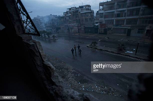 Syrians walk along a street following evening prayers at the alNasr mosque in the city of Aleppo on January 6 2013 Syria's embattled President Bashar...