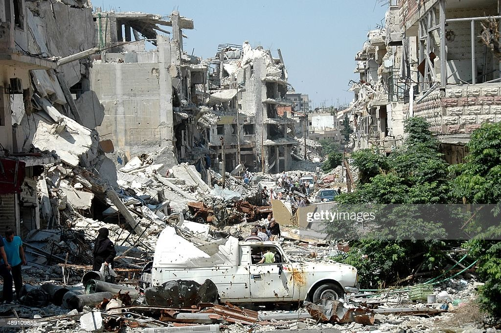 Syrians walk amid debris as they return to the Juret alShayah district of the central city of Homs on May 10 a day after the last Syrian rebels left...