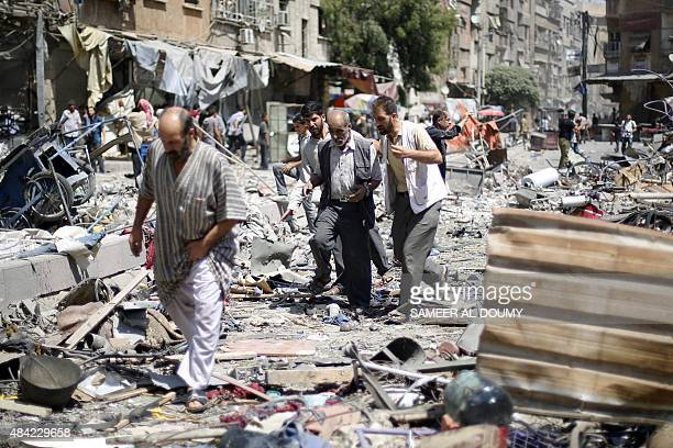 Syrians walk amid the rubble following air strikes by Syrian government forces on a marketplace in the rebelheld area of Douma east of the capital...