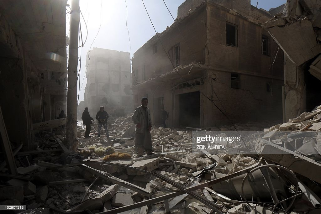 Syrians walk amidst the rubble in search for survivors following a reported air strike by Syrian government forces in the Maysar neighbourhood of the...