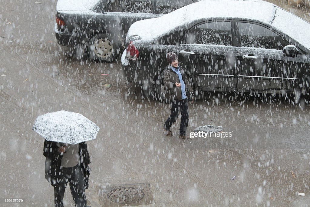 Syrians walk in central Damascus during snow fall on January 9, 2013 as a fierce storm whipped the region this week and temperatures dropped dramatically.