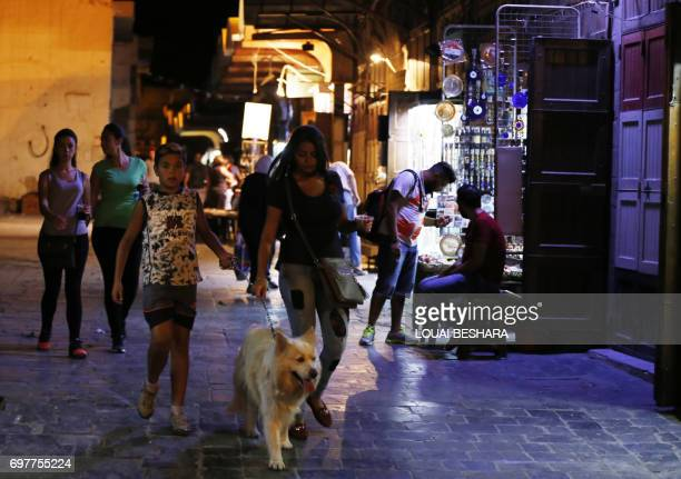 Syrians walk in the old city of the capital Damascus on June 19 2017 / AFP PHOTO / Louai Beshara