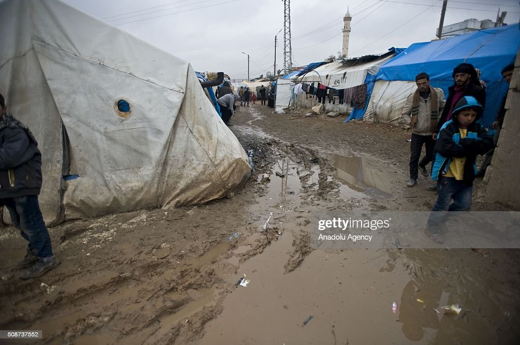 Syrians walk on mud covered road at tent city built by IHH Humanitarian Relief Foundation near the Bab al-Salam border gate on Turkey's border in Azez district of Aleppo as they flee to Turkey to escape heavy Syrian regime and Russian airstrikes, on February 6, 2016.