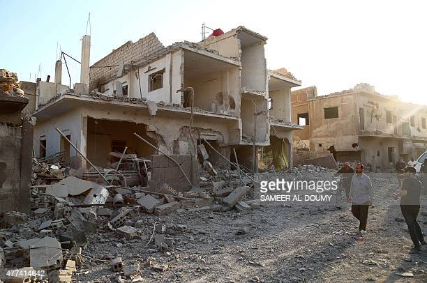 Syrians walk past a building destroyed in a reported air strike by government forces on the rebelheld town of Douma northeast of the capital Damascus...