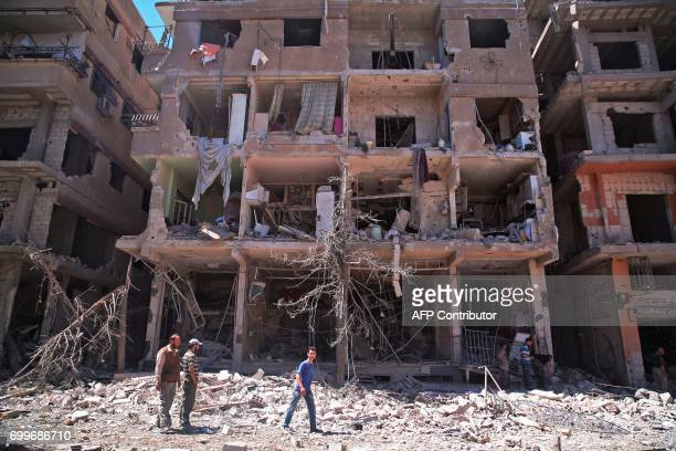 Syrians walk past a damaged building in Ain Tarma in the eastern Ghouta area a rebel stronghold east of the capital Damascus on June 21 2017 / AFP...