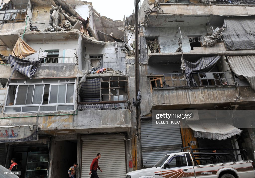 Syrians walk past a partially destroyed building in the northern city of Aleppo on March 22, 2013. The UN lamented the escalating violence in Syria and extended a probe into widespread human rights violations in the war-torn country.