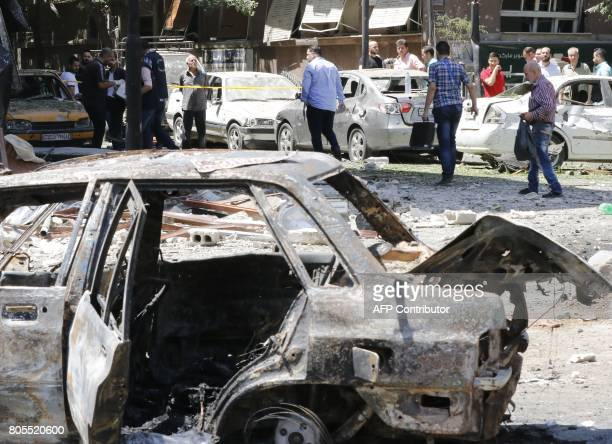 Syrians walk past charred vehicles at the site of a suicide bomb attack in the capital Damascus' eastern Tahrir Square district on July 2 2017 Syrian...
