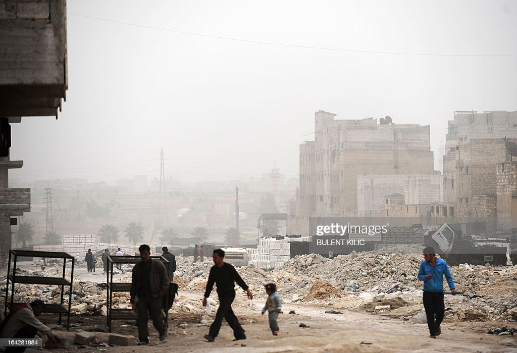 Syrians walk past destruction in the northern city of Aleppo on March 22, 2013. The UN lamented the escalating violence in Syria and extended a probe into widespread human rights violations in the war-torn country.