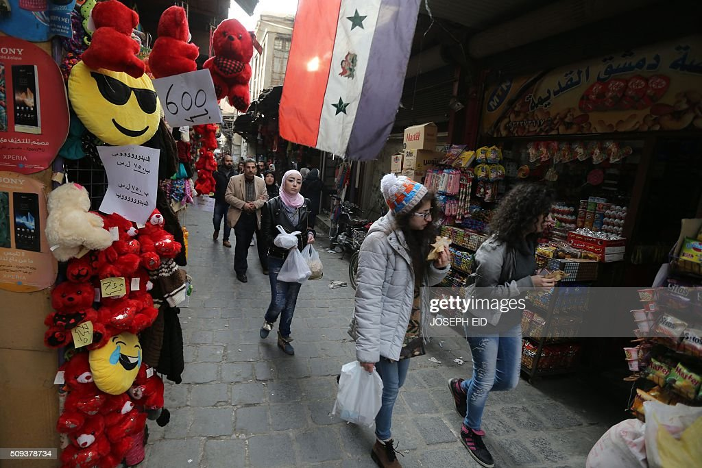 Syrians walk past shops displaying red teddy bears and gifts for Valentine's day in Damascus on February 10, 2016. / AFP / JOSEPH EID