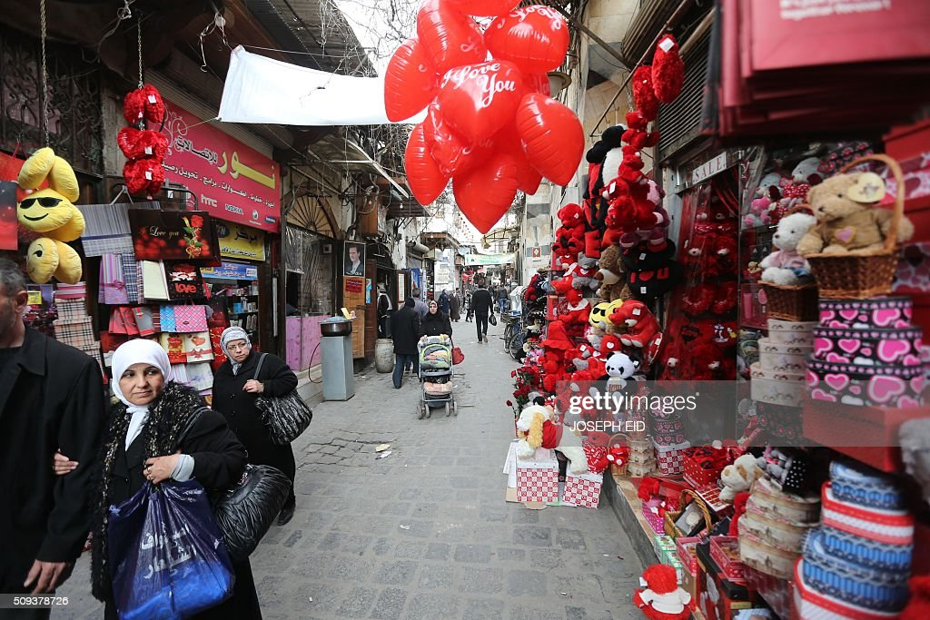 Syrians walk past shops displaying red teddy bears, balloons and gifts for Valentine's day in Damascus on February 10, 2016. / AFP / JOSEPH EID