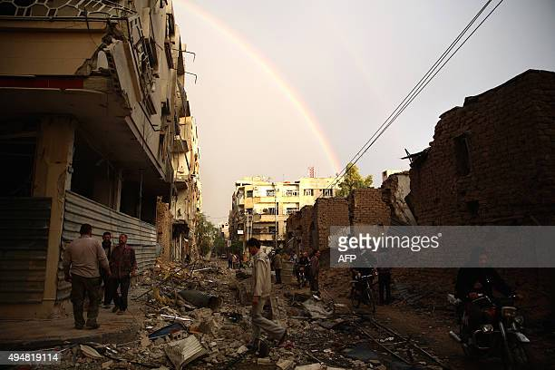 Syrians walk through debris following a reported air strike by Syrian government forces in the rebelheld town of Douma east of the capital Damascus...