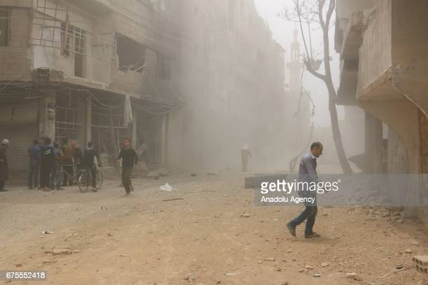 Syrians walk through smoke after Assad Regime's airstrike hit residential areas at the Saqba town of Eastern Ghouta in Damascus Syria on May 1 2017
