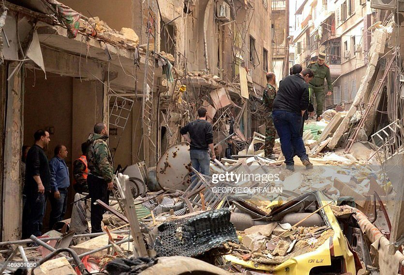 Syrians walk through the rubble following reported rocket attacks by rebel fighters on the Christian neighbourhood of Suleimaniyah in northern Aleppo...