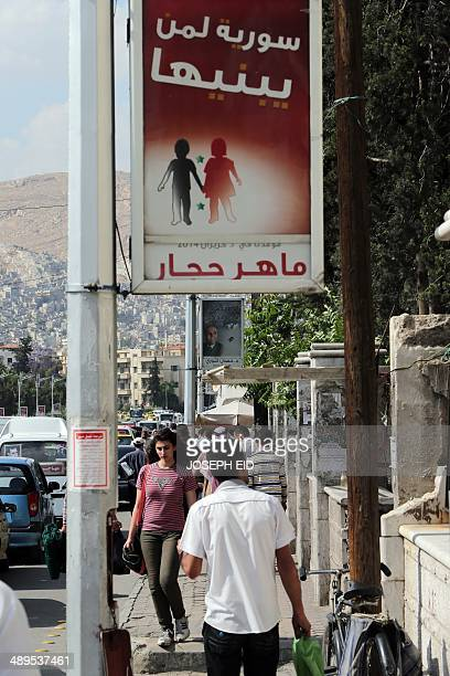 Syrians walk under election campaign billboards of presidential candidates Hassan Abdallah alNuri and Maher Abdel Hafiz Hajjar on May 11 2014 in a...