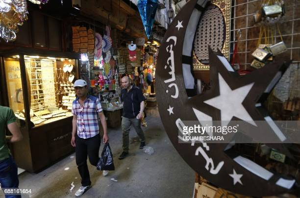 Syrians walks past traditional lanterns known in Arabic as 'Fanous' sold during Ramadan in the old city of Damascus on May 25 ahead of the start of...
