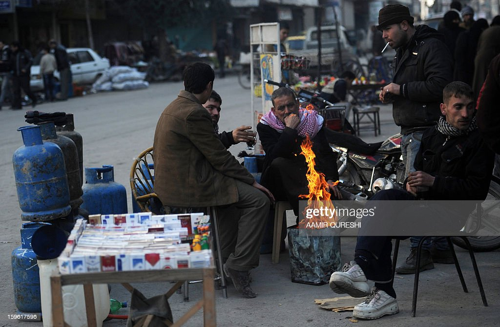 Syrians warm themselves around a fire in Aleppo's old city on January 17, 2013. Rebels trying to break a months-long deadlock in their battle for Syria's second city Aleppo say they are cutting supply routes ahead of simultaneous assaults on regime bases. AFP PHOTO/AAMIR QURESHI