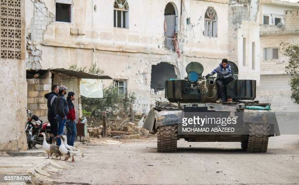 Syrians watch as another man rides on the turret of a movin tank in the rebelheld area of Daraa in southern Syria on February 4 2017 / AFP / MOHAMAD...