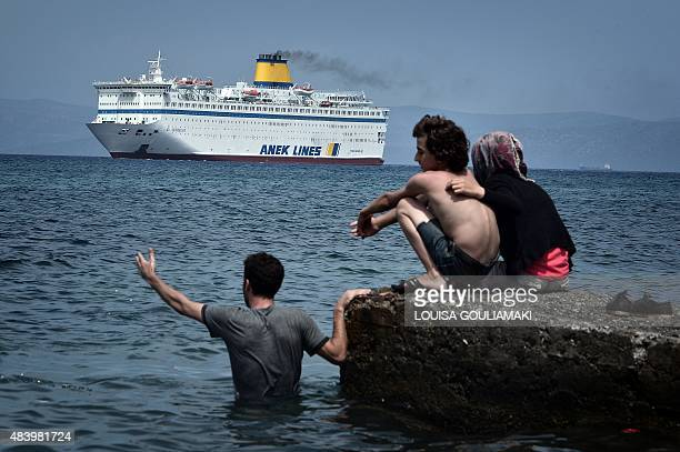 Syrians watch the Eleftherios Venizelos ferry arriving at the Greek port on the island of Kos which will be a temporary accomodation and registration...