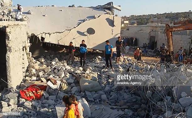 Syrians watch the search and rescue operation undertaken by civil defense teams among the ruins of destroyed building in a region of Idlib a...
