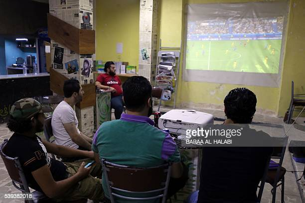 Syrians watch the UEFA Euro 2016 opening football match between France and Romania in the Salaheddine district of the northern embattled city of...