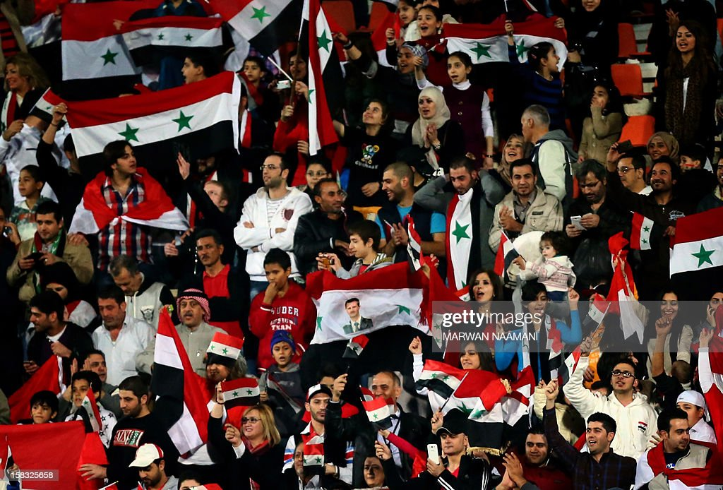 Syrians wave their national flag and chant slogans in support of their embattled President Bashar al-Assad (portrait-C) during their country's team football match against Iraq in the 7th West Asia Football Federation (WAFF) championship in Kuwait City on December 13, 2012.