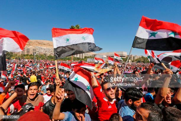 Syrians wave their national flag and cheer on their national team at the Umayyad Square in Damascus as they watch a broadcast of the World Cup...
