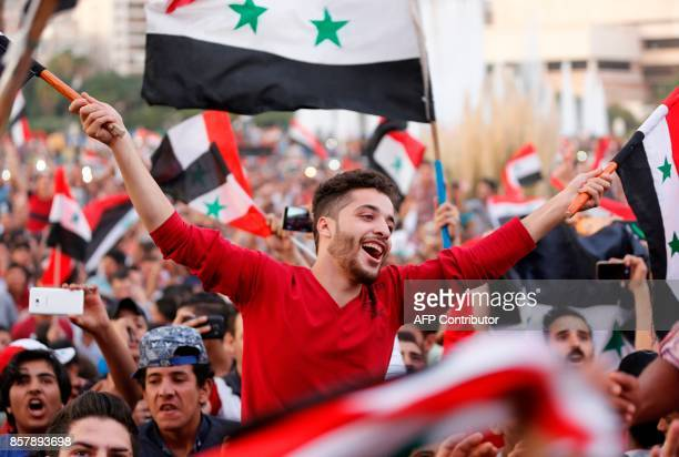 TOPSHOT Syrians wave their national flag as they celebrate in Damascus' Umayyad Square on October 5 after Syria's national football team scored in...