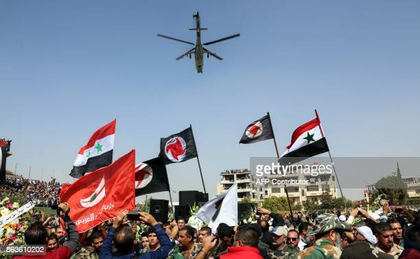TOPSHOT Syrians wave their national flags and those of the Syrian Social Nationalist Party in a stadium as a Russianmade Mil Mi24 helicopter gunship...