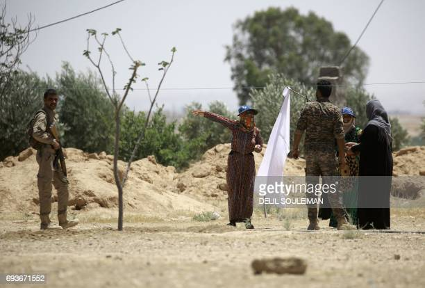CORRECTION Syrians waving a white flag talk with members of the Syrian Democratic Forces made up of an alliance of Kurdish and Arab fighters as they...