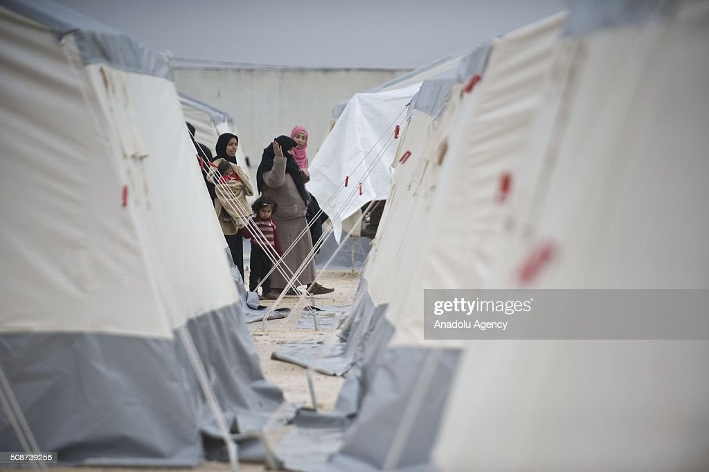 Syrians who fled bombing in Aleppo, are seen near tents, which were distributed by the IHH Humanitarian Relief Foundation, a Turkish NGO, at the Oncupinar crossing, opposite the Turkish province of Kilis, near Azaz town of Aleppo, Syria on February 6, 2016. Thousands of Syrians have massed on the Syrian side of the border seeking refuge in Turkey.