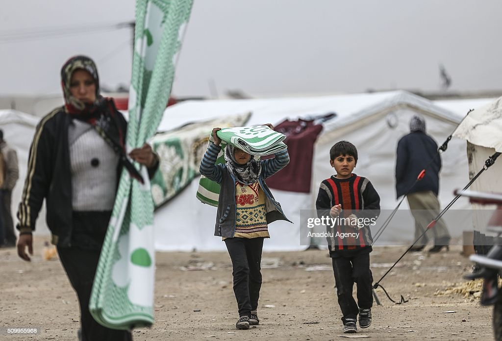 Syrians, who fled bombing in Aleppo, carry rush mats which were distributed by Turkish humanitarian aid organizations at a tent city close to the Bab al-Salam border crossing on Turkish-Syrian border near Azaz town of Aleppo, Syria on February 13, 2016. Russian airstrikes have recently forced some 40,000 people to flee their homes in Syrias northern city of Aleppo.