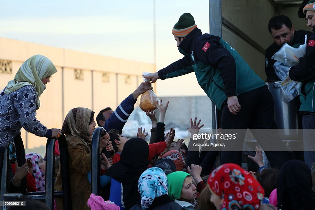 Syrians, who fled bombing in Aleppo, try to get food at a tent city close to the Bab al-Salam border crossing on Turkish-Syrian border near Azaz town of Aleppo, Syria on February 10, 2016. Russian airstrikes have recently forced some 40,000 people to flee their homes in Syrias northern city of Aleppo.