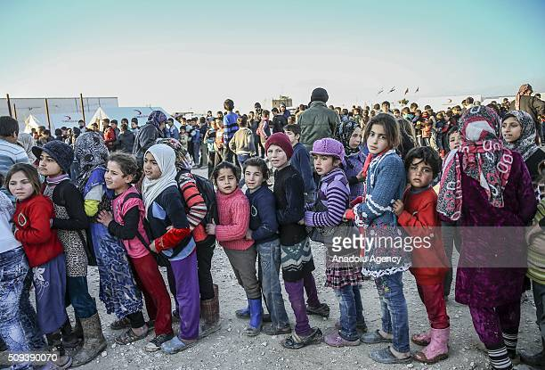 Syrians who fled bombing in Aleppo wait in a queue to get food at a tent city and close to the Bab alSalam border crossing on TurkishSyrian border...