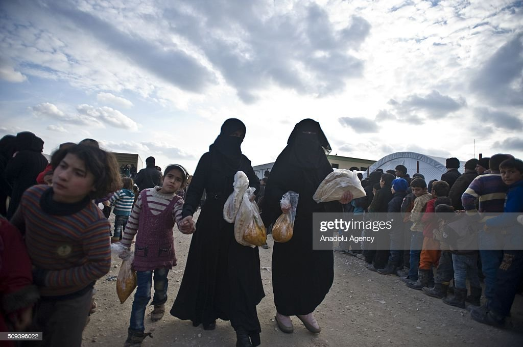 Syrians, who fled bombing in Aleppo, wait in a queue to get food at a tent city close to the Bab al-Salam border crossing on Turkish-Syrian border near Azaz town of Aleppo, Syria on February 10, 2016. Russian airstrikes have recently forced some 40,000 people to flee their homes in Syrias northern city of Aleppo.