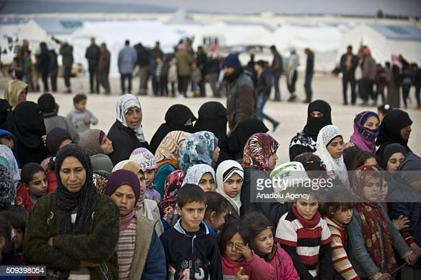 Syrians who fled bombing in Aleppo wait in a queue to get food at a tent city close to the Bab alSalam border crossing on TurkishSyrian border near...