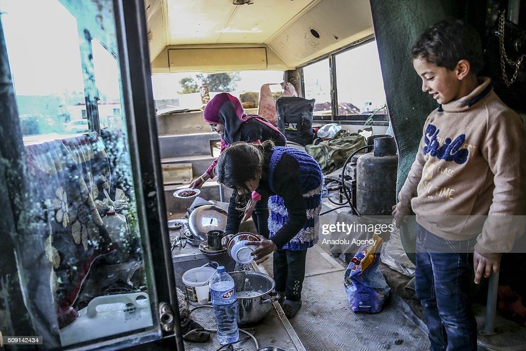 Syrians who flee the attacks of Assad Regime and Russian air forces, try to live inside wrecked vehicle as they barely covered them with blankets and tarpaulins, at a refugee camp at the Bab al-Salameh border crossing on Turkish-Syrian border near Azaz town of Aleppo, Syria on February 09, 2016.