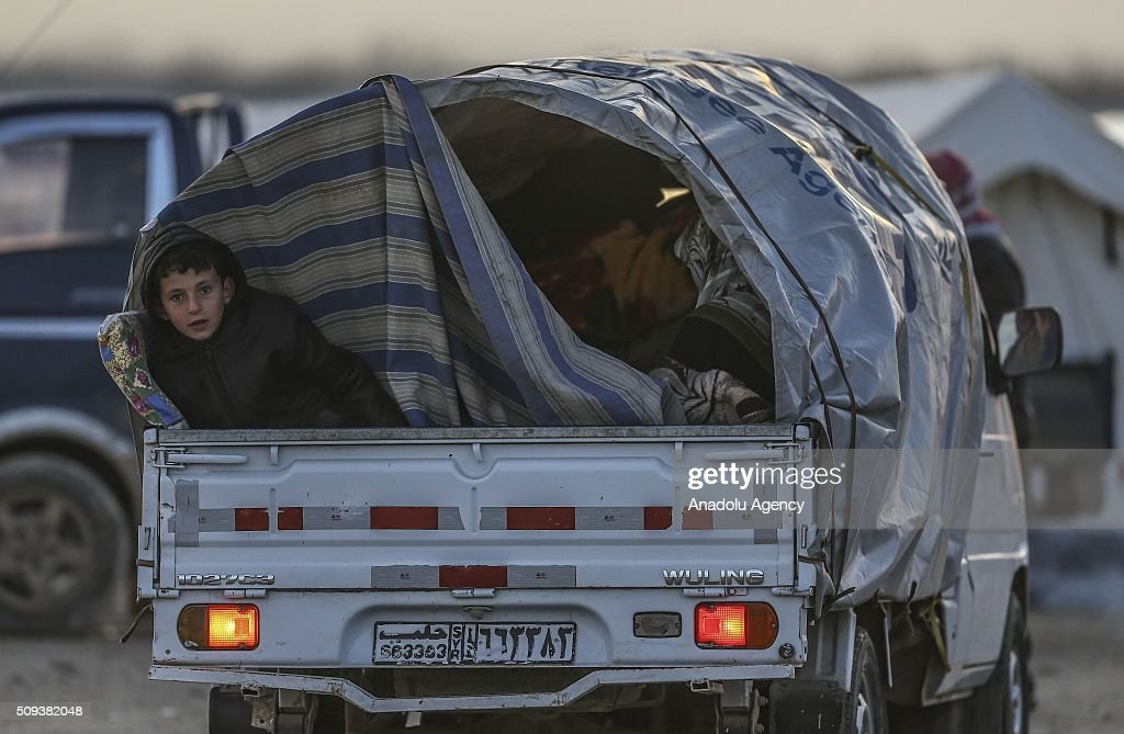 Syrians who flee the attacks of Syrian and Russian air forces, shelter at vehicles and try to live their lives with humanitarian aid send by Turkey, UNHCR and other Turkish Humanitarian aid organizations, close to the Bab al-Salameh border crossing on Turkish-Syrian border near Azaz town of Aleppo, Syria on February 10, 2016.