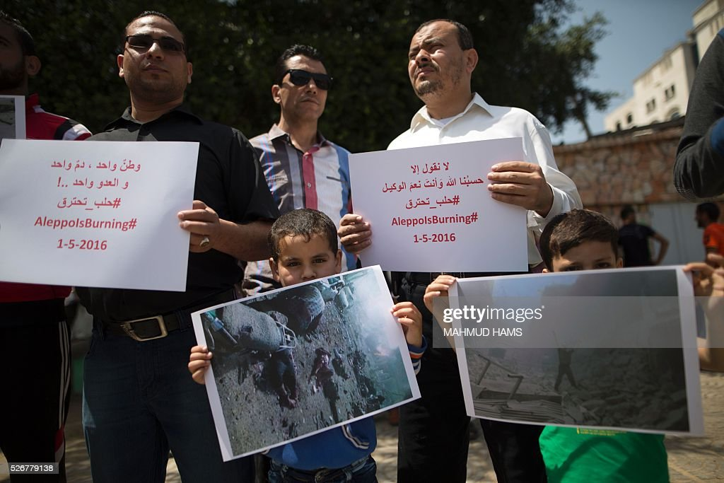 Syrians who live in the Gaza Strip after fleeing their war-hit country hold placards during a rally against Syrian government shelling on the northern city of Aleppo, on May 1, 2016, in Gaza City. / AFP / MAHMUD