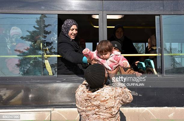TOPSHOT Syrians who were evacuated from Fuaa and Kafraya two Shiite villages under rebelsiege on the northern outskirts of Idlib are welcomed by...