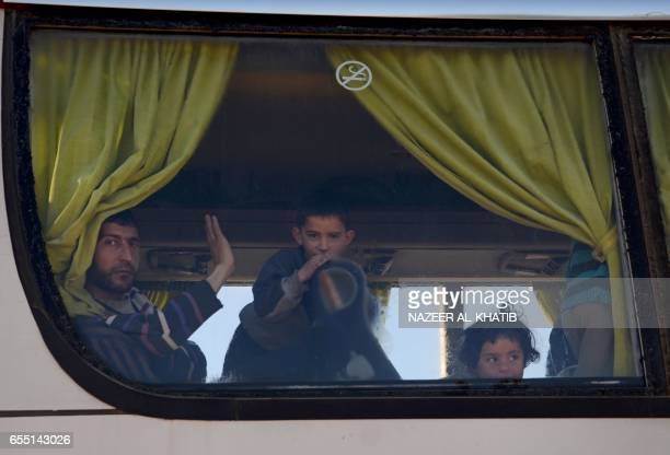 TOPSHOT Syrians who were evacuated from Waer the last oppositionheld district of Homs arrive in the northern Syrian town of alBab on March 19 under a...