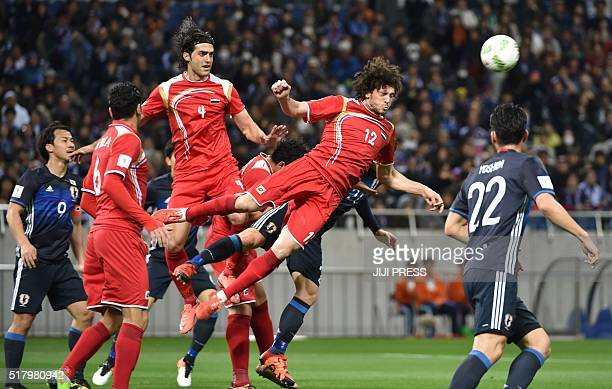 Syria's defender Omro Al Midani clears the ball against Japan during the 2018 World Cup qualifier Asian secondround Group E football match between...